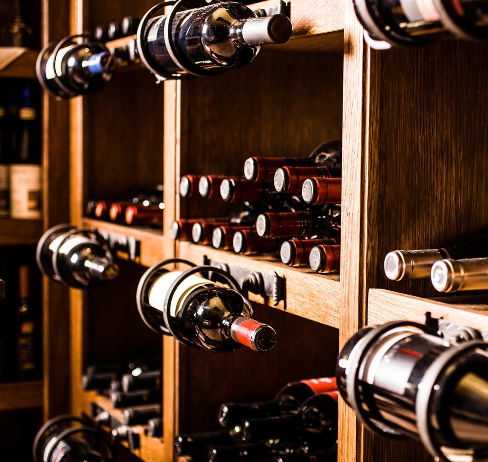Arredamento enoteca: bottiglie appese alle mensole